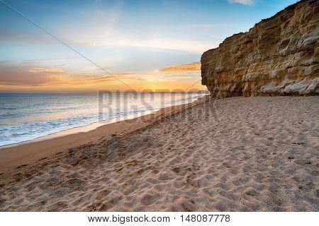 Sunset over Hive Beach at cliffs at Burton Bradstock near Bridport on the Dorset coastline