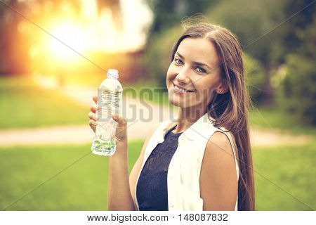 Portrait of young beautiful dark haired woman drinking water at summer green park