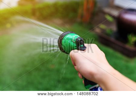 water hose or spray into the green garden yard at sunset