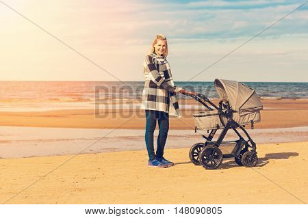 smiling young mother with baby carriage on the beach