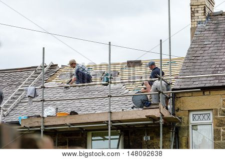 WREXHAM WALES UNITED KINGDOM - AUGUST 10 2016: Restoration of decorative slate roof on a residential terraced house in North Wales. With three workmen.