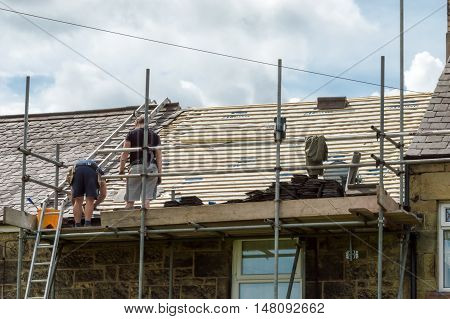 WREXHAM WALES UNITED KINGDOM - AUGUST 05 2016: Restoration of decorative slate roof on a residential terraced house in North Wales. With workmen.