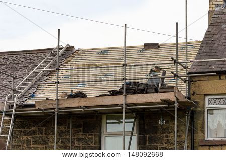 WREXHAM WALES UNITED KINGDOM - AUGUST 05 2016: Restoration of decorative slate roof on a residential terraced house in North Wales.