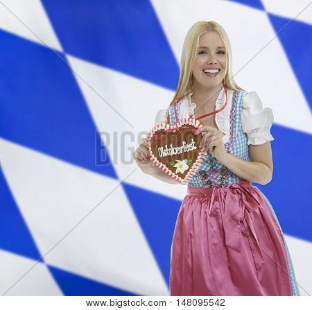 Smiling bavarian woman in traditional clothing with an Oktoberfest Gingerbread heart with a bavarian flag in the background