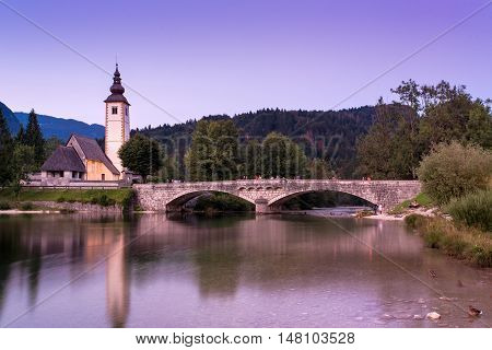 BOHINJ LAKE SLOVENIA - AUGUST 25 2016: Church of St. John the Baptist at Bohinj Lake is over 700 years old and is a beautiful example of Middle Age architecture and fresco painting in Slovenia.