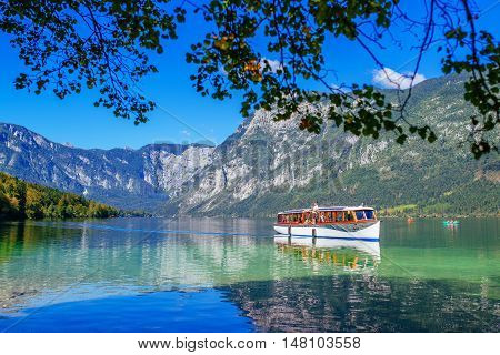 RIBCEV LAZ SLOVENIA - AUGUST 24 2016: Tourists sightseeing Slovenian Bohinj lake and surrounding in Triglav national park from tourist boat
