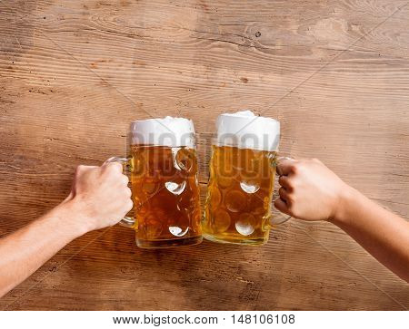 Hands of two unrecognizable men clinking with beer mugs. Oktoberfest. Studio shot on brown wooden background. Copy space. poster