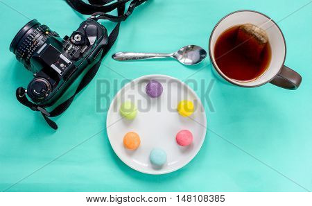 colorful french macaron,cup of tea and SLR camera on green background-Top view