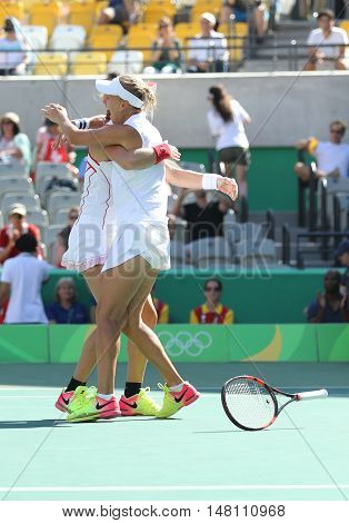 RIO DE JANEIRO, BRAZIL - AUGUST 14, 2016: Ekaterina Makarova (L) and Elena Vesnina of Russia celebrate victory after women's doubles final of the Rio 2016 Olympic Games at the Olympic Tennis Centre