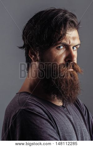 Young man hipster with bearded gloom frown handsome face and dark hair in fashion shirt posing on gray background studio