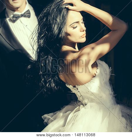 Beautiful bride in light and groom as married couple in wedding dress and suit pose outdoors on streetscape background