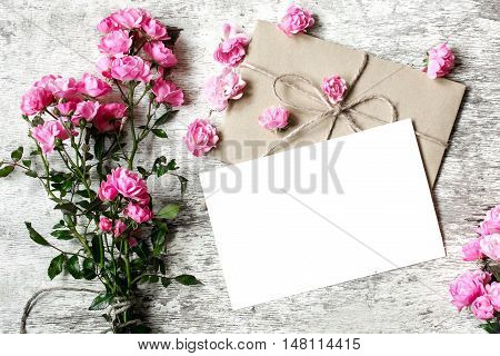 Bouquet of tender pink roses with a blank greeting card and envelope on white rustic wooden background with copy space. holiday background