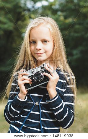 Cute little girl with a vintage rangefinder camera. Beautiful long blond hair.