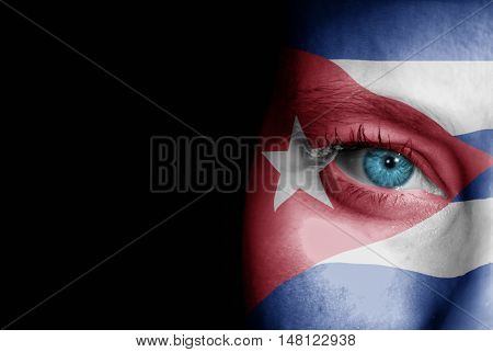 A young female with the flag of Cuba painted on her face on her way to a sporting event to show her support.