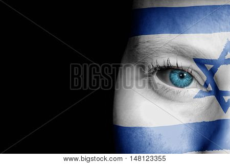 A young female with the flag of Israel painted on her face on her way to a sporting event to show her support.
