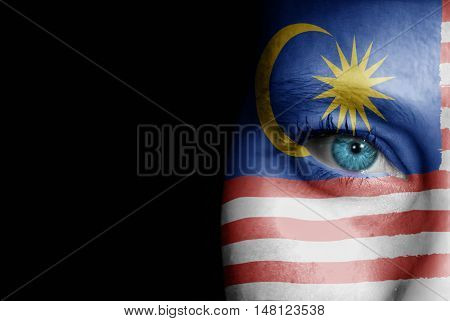 A young female with the flag of Malaysia painted on her face on her way to a sporting event to show her support.