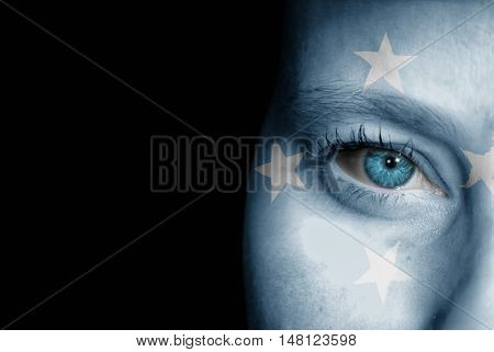 A young female with the flag of Micronesia painted on her face on her way to a sporting event to show her support.