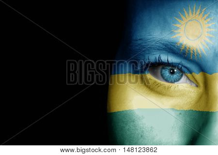 A young female with the flag of Rwanda painted on her face on her way to a sporting event to show her support.