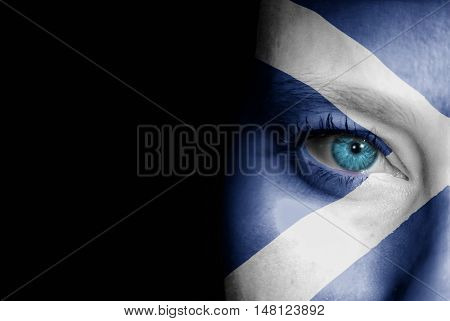 A young female with the flag of Scotland painted on her face on her way to a sporting event to show her support.