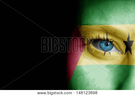 A young female with the flag of Sao Tome and Principe painted on her face on her way to a sporting event to show her support.