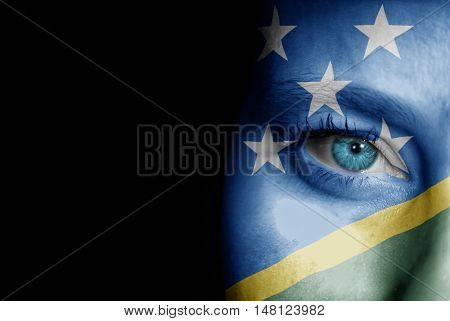 A young female with the flag of Solomon Islands painted on her face on her way to a sporting event to show her support.