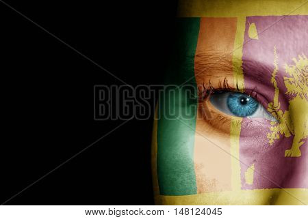 A young female with the flag of Sri Lanka painted on her face on her way to a sporting event to show her support.