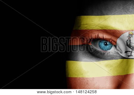 A young female with the flag of Uganda painted on her face on her way to a sporting event to show her support.
