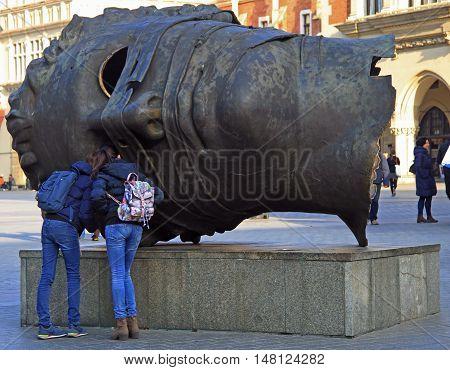 Krakow, Poland - October 29, 2015: tourists are exploring head sculpture Eros Bendato by polish artist Igor Mitoraj on Market Square in Krakow, Poland