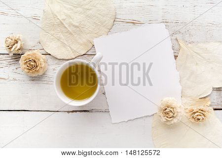 flowers on a white wooden table with blank pages and a cup of green tea. Copy space. Free space for text. Top view