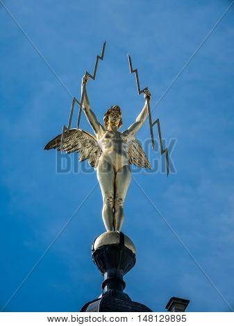 Golden statue of a winged 'Electrica' on top of a landmark building along Meir street in Antwerp, Belgium