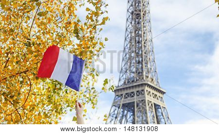Having fun time near the world famous landmark in Paris. Closeup on smiling elegant child on embankment near Eiffel tower in Paris France rising flag while sitting on the parapet