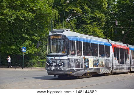 POLAND, KRAKOW - MAY 27, 2016: Tram Bombardier-Rotax/MPK EU8N in the historic part of Krakow. Total in Krakow more than 90 kilometers of tram tracks and 24 routes.