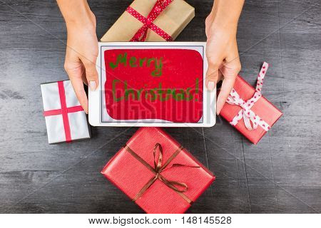 Closeup Of Gifts On Table With Tablet And Merry Christmas Words