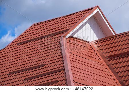 The roof of corrugated sheet red orange. Roofing of metal profile wavy shape. poster