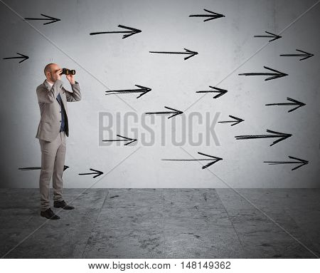 Man looks through binoculars with arrows on the wall
