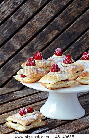 Millefeuille dessert with raspberry on the dark background, french dessert on the cake stand