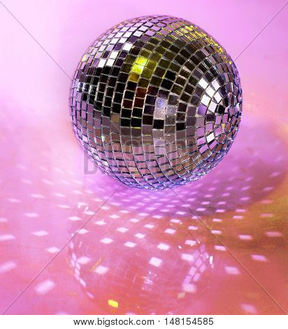 mirrored disco ball on a purple and pink background
