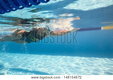 Athletic female swimmer swims underwater in the swimming pool outdoors. She wears a black-gray swimsuit with patterns, a white swim cap and swim glasses. Sunlight falls from above. Horizontal.