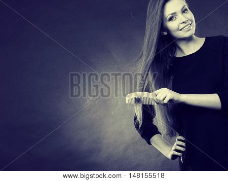 Preparation to evening party. Gorgeous attractive woman combing her long straight smoothy healthy hair before go out. Party and celebration concept.