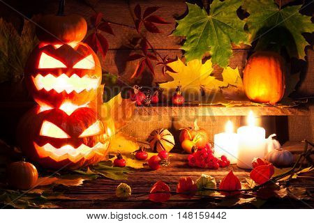Halloween pumpkin head jack lantern with burning candles over wooden background