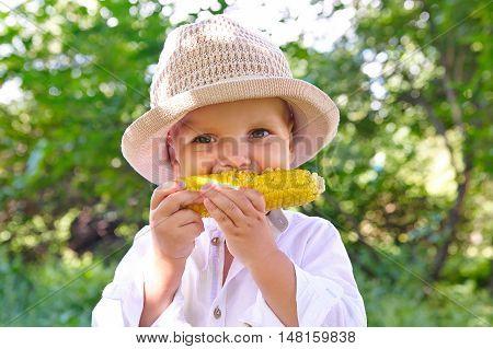 Adorable young boy eating corn on the cob