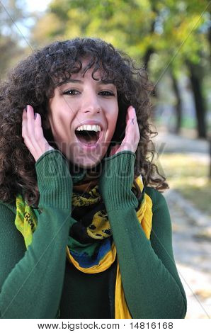 Young curly woman screeming outdoors in nature