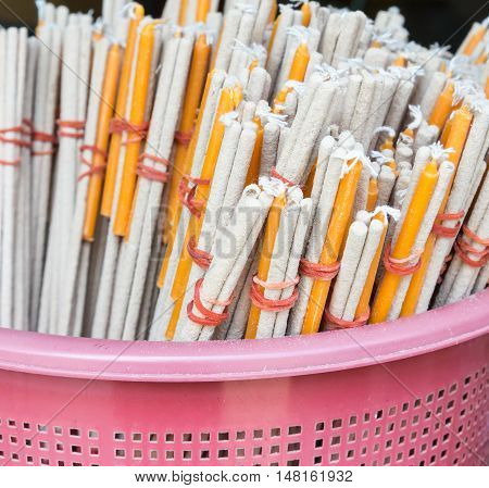 Incense stick and candle set in the plastic basket for pray the Buddha statue.(Select focus)
