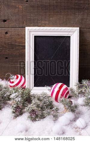 Empty blackboard christmas balls and branches fur tree on aged wooden background. Decorative christmas composition. Selective focus. Place for text.