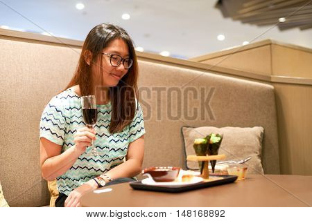 SINGAPORE - CIRCA SEPTEMBER, 2016: indoor portrait of a woman in Plaza Premium Lounge at Singapore Changi Airport. Changi Airport is the primary civilian airport for Singapore.