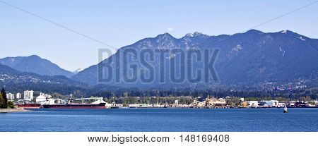 Long panorama shot of North Vancouver accross Vancouver Harbour on a bright sunny day, blue sky with the majestic Rockies rising in the background. View of the shipping port industry, buildings and a large cargo ship coasting in to unload.
