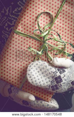 Girl holds in hands Christmas present. Christmas background. Gifts for men. Knitted mittens. Knitted dress. Box with gifts. Merry Christmas. Toned image.