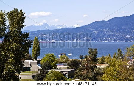 View of Vancouver's English Bay from the Burrard Bridge with the Rockies rising majectically as a backdrop on a gorgeous sunny day with blue skies and few clouds. Cargo ships and boats are in the bay and trees are in the foreground