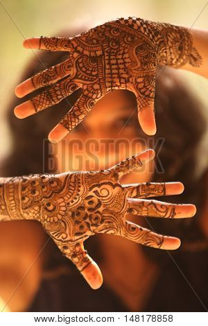 The hands of an Indian bride beautifully covered with mehendi/henna as a traditional ritual on the wedding eve.