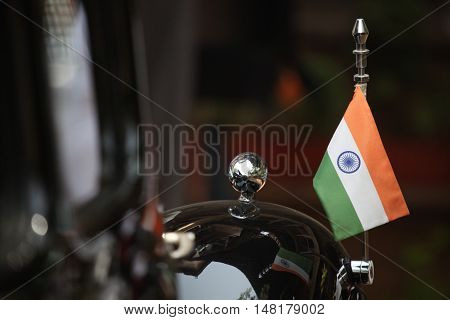 An Indian flag put up on a black vintage car used by the Indian government